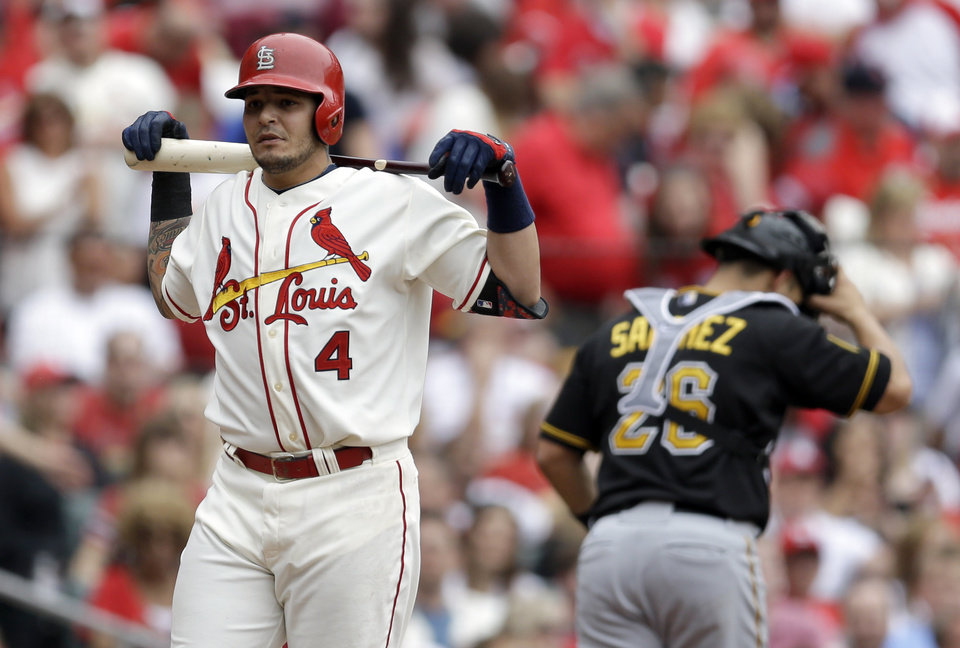 Photo - St. Louis Cardinals' Yadier Molina, left, and Pittsburgh Pirates catcher Tony Sanchez walk off the field after Molina struck out with the bases loaded to end the third inning of a baseball game Saturday, April 26, 2014, in St. Louis. (AP Photo/Jeff Roberson)