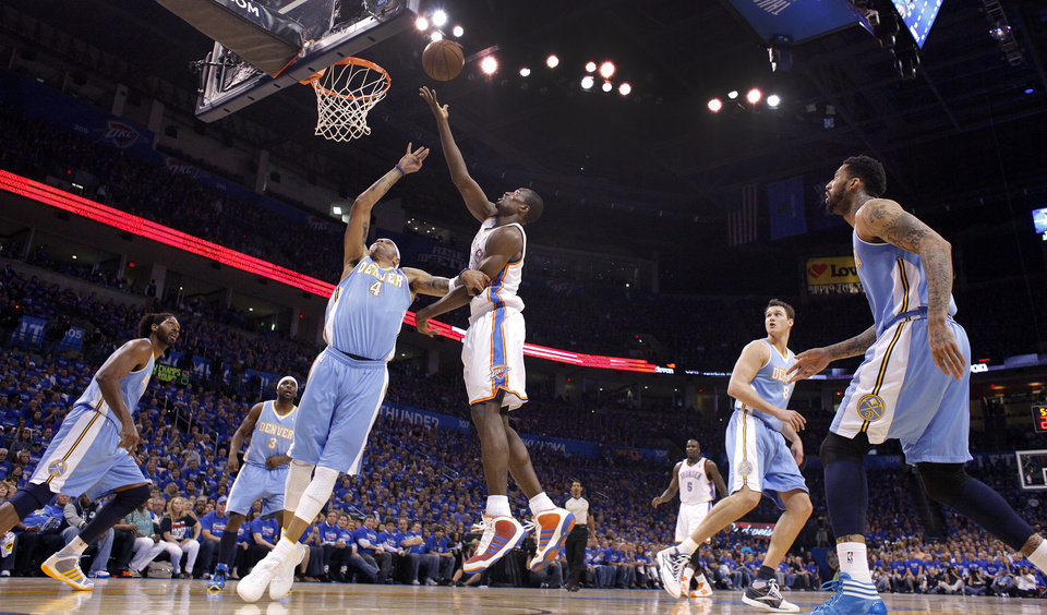 Photo - Oklahoma City's Serge Ibaka (9) lays up a shot over Denver's Kenyon Martin (4) during the first round NBA playoff game between the Oklahoma City Thunder and the Denver Nuggets on Sunday, April 17, 2011, in Oklahoma City, Okla. Photo by Chris Landsberger, The Oklahoman