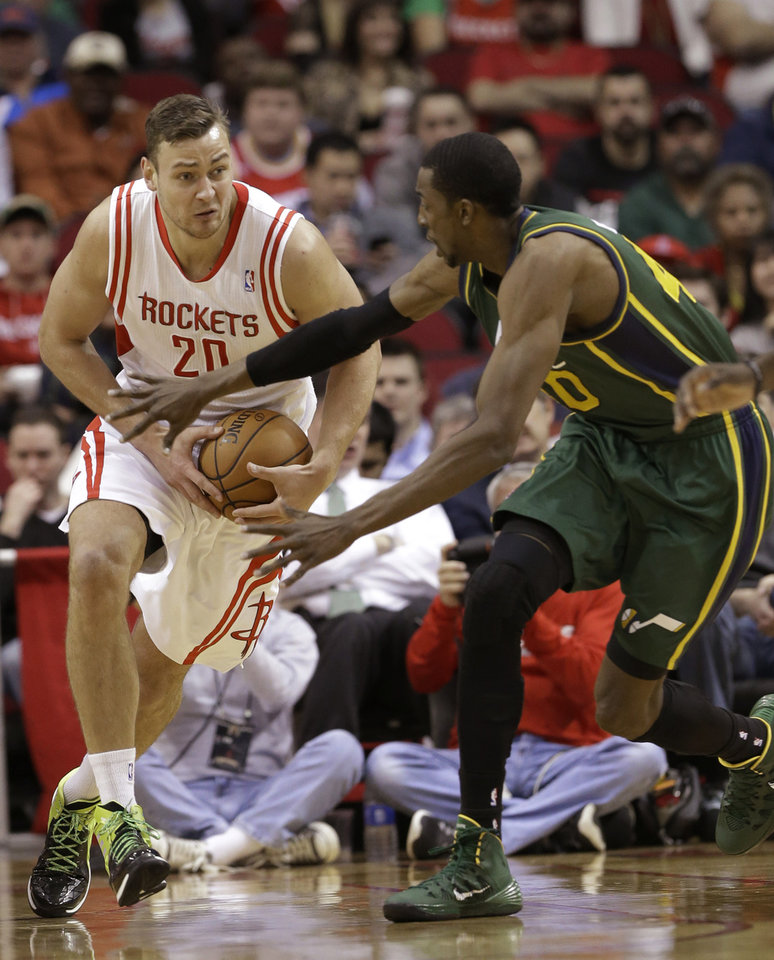 Photo - Utah Jazz's Jeremy Evans (40) tries to grab the ball from Houston Rockets's Donatas Motiejunas (20) in the first half of an NBA basketball game Monday, March 17, 2014, in Houston. (AP Photo/Pat Sullivan)