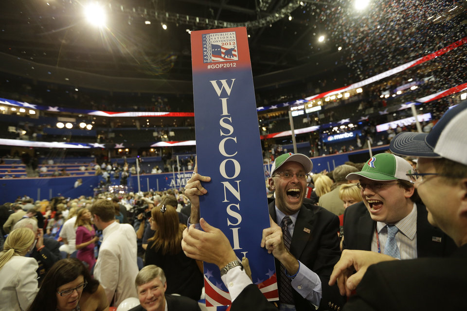 Photo -   Justin Johnson of Chippewa Falls, Wis., celebrates after removing his state's sign after Republican presidential candidate Mitt Romney and vice presidential candidate Paul Ryan left the stage at the end of the Republican National Convention in Tampa, Fla., on Thursday, Aug. 30, 2012. (AP Photo/David Goldman)