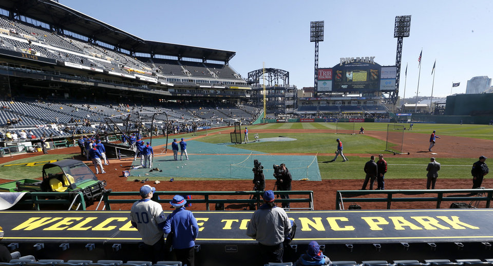 Photo - Chicago Cubs fans stand behind the first base dugout at PNC Park in Pittsburgh as their team takes batting practice before their opening day baseball game against the Pittsburgh Pirates on Monday, March 31, 2014, . (AP Photo/Keith Srakocic)
