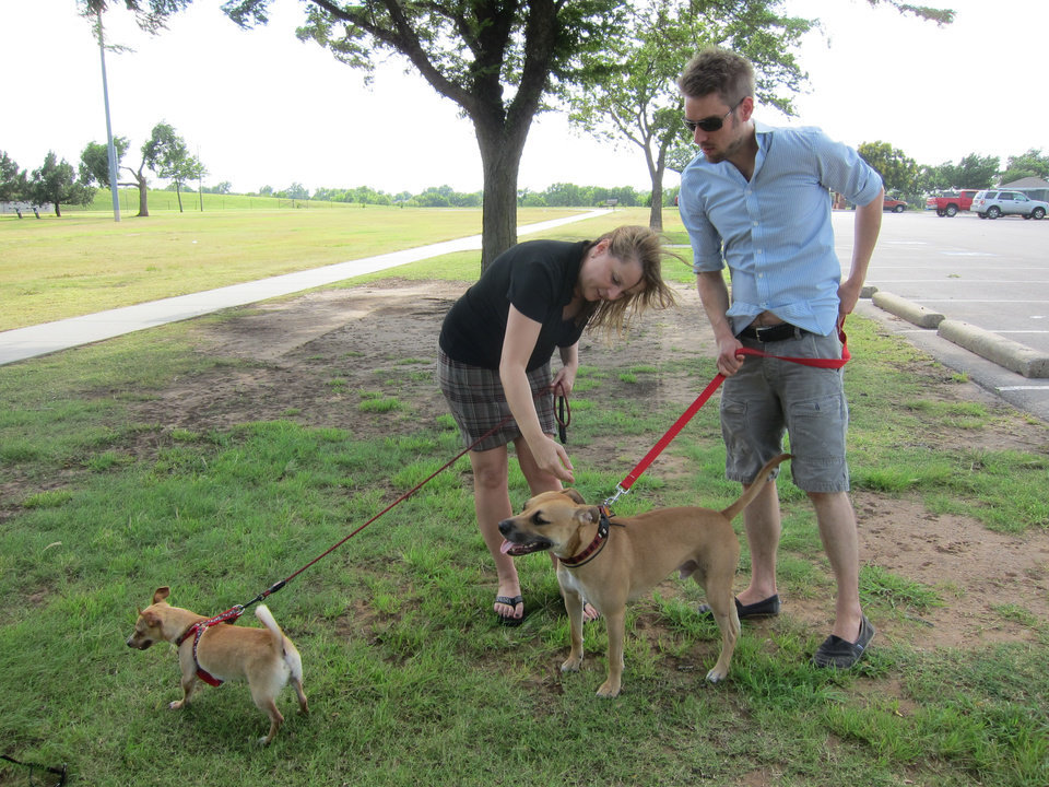 Photo -  Meike Parker and Jared White, founders of The Underdogs Rescue Inc., are pictured with their dogs at the Oklahoma City Paw Park at 3303 NW Grand Blvd. Photo by Carla Hinton, The Oklahoman