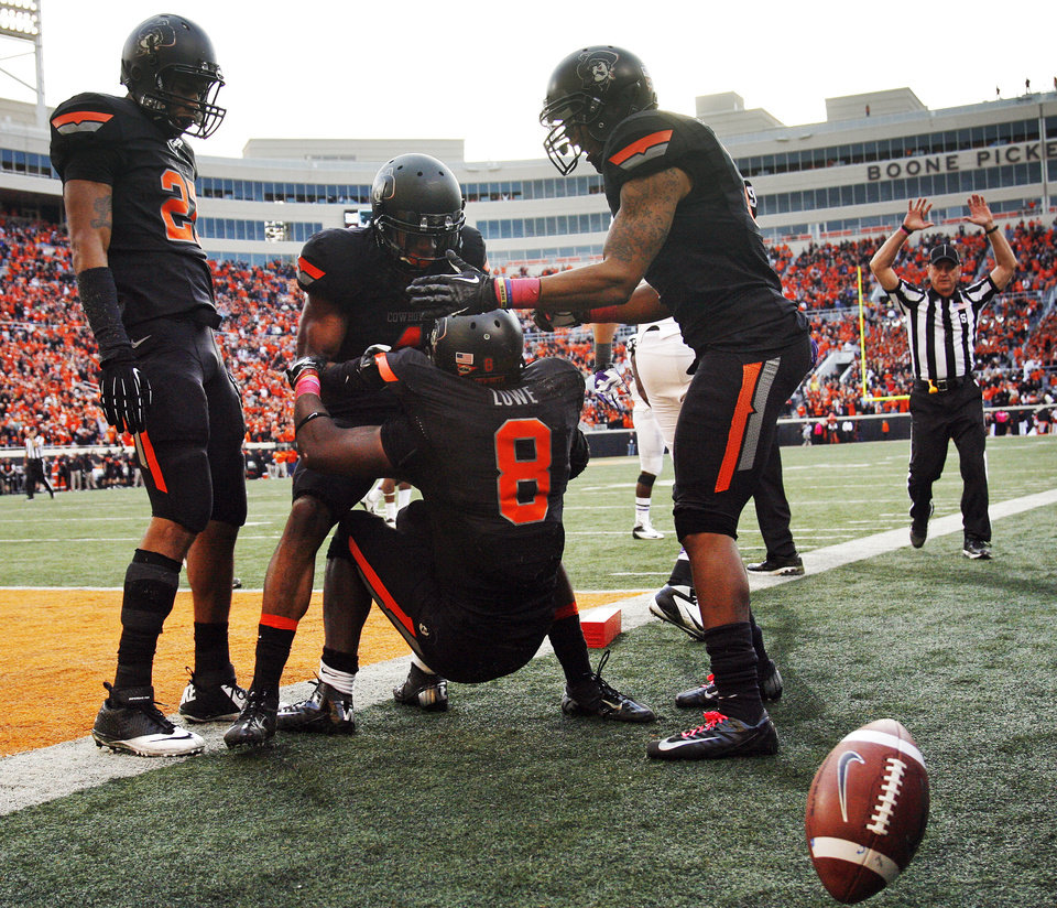 Photo - From left, Oklahoma State's Lyndell Johnson (27), Justin Gilbert (4) and Shamiel Gary (7) help Daytawion Lowe (8) up after Lowe returned an interception to the 1-yard line in the fourth quarter during a college football game between Oklahoma State University (OSU) and Texas Christian University (TCU) at Boone Pickens Stadium in Stillwater, Okla., Saturday, Oct. 27, 2012. OSU won, 36-14. Photo by Nate Billings, The Oklahoman