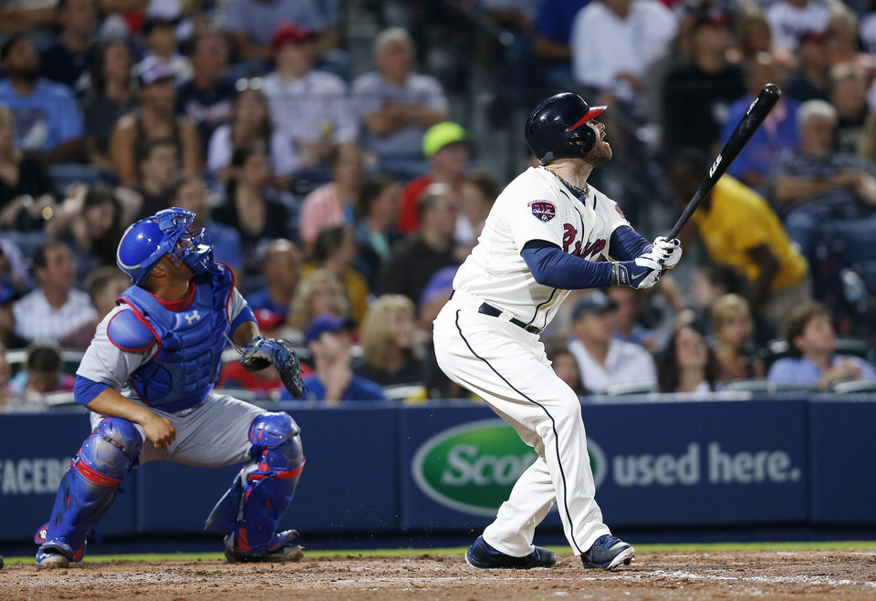Photo - Atlanta Braves pitch hitter Ryan Doumit (4) follows through with an RBI double as Chicago Cubs catcher Welington Castillo (5) looks on in the seventh inning of a baseball game Saturday, May 10, 2014 in Atlanta.  (AP Photo/John Bazemore)