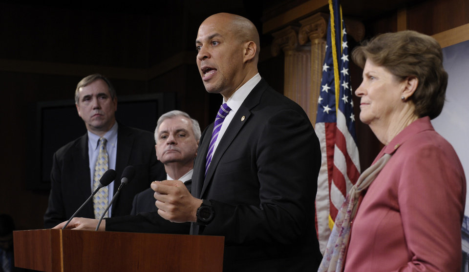 Photo - Sen. Cory Booker, D-N.J., second from right, speaks during a news conference to discuss unemployment insurance, Thursday, Feb. 6, 2014, on Capitol Hill in Washington. From left are, Sen. Jeff Merkley, D-Ore., Sen. Jack Reed, D-R.I., Booker and Sen. Jeanne Shaheen, D-N.H.  (AP Photo/Susan Walsh)