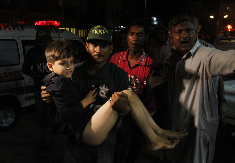 Photo - Pakistani volunteers rush an injured boy to hospital following an explosion in Karachi, Pakistan on Friday, April 26, 2013. A bomb planted near the office of a political party threatened by the Taliban has killed many people in southern Pakistan, police said. (AP Photo/Shakil Adil)