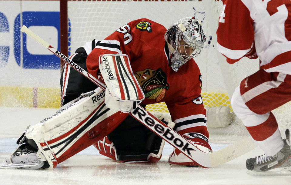 Photo - Chicago Blackhawks goalie Corey Crawford (50) makes a save during the first period of Game 1 of an NHL hockey playoffs Western Conference semifinal against the Detroit Red Wings in Chicago, Wednesday, May 15, 2013. (AP Photo/Nam Y. Huh)