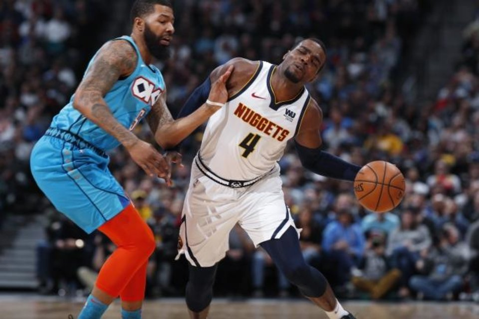 Photo -  Denver forward Paul Millsap, right, reacts as he drives past Oklahoma City forward Markieff Morris during the Nuggets' 121-112 win on Feb. 26. [AP Photo/David Zalubowski]
