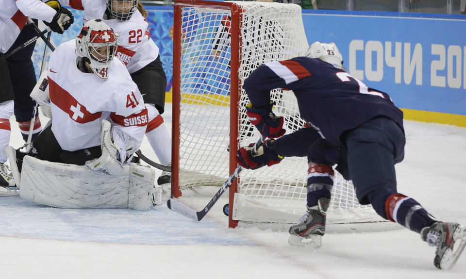Photo - Goalkeeper Florence Schelling of Switzerland watches as Amanda Kessel of the Untied States shoot slides in for the goal during the first period of the 2014 Winter Olympics women's ice hockey game at Shayba Arena, Monday, Feb. 10, 2014, in Sochi, Russia. (AP Photo/Matt Slocum)