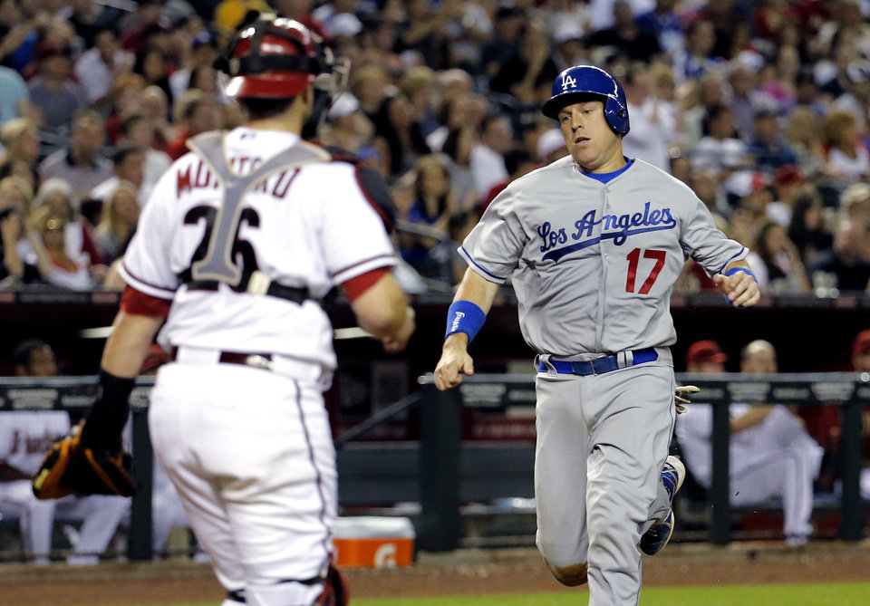 Photo - Los Angeles Dodgers' A.J Ellis scores on a double hit by teammate Zack Greinke as Arizona Diamondbacks' Miguel Montero waits for the throw during the fourth inning of a baseball game on Friday, May 16, 2014, in Phoenix. (AP Photo/Matt York)