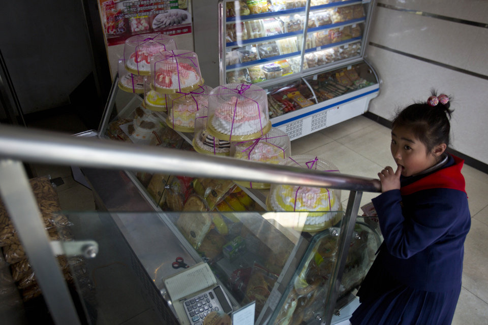 Photo - In this Feb. 16, 2013 photo, a North Korean girl stands inside a cake shop in Pyongyang, North Korea. (AP Photo/David Guttenfelder)