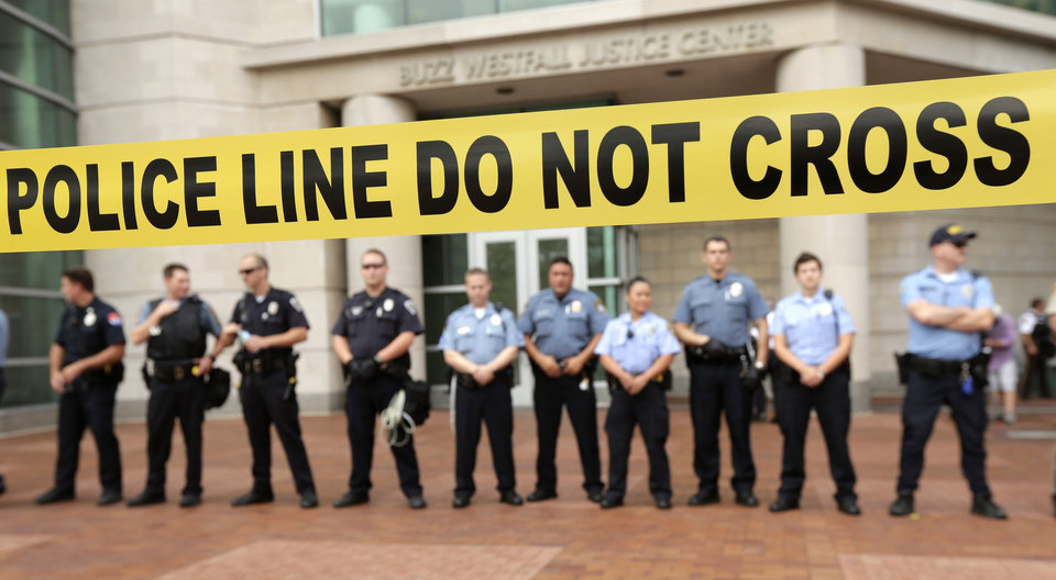 Photo - Police guard the entrance to the Buzz Westfall Justice Center in Clayton, Mo., Wednesday, Aug. 20, 2014, where a grand jury is expected to convene to consider possible charges against the Ferguson, Mo. police officer who fatally shot 18-year-old Michael Brown. Brown's shooting in the middle of a street has sparked a more than week of protests, riots and looting in the St. Louis suburb. (AP Photo/Charlie Riedel)