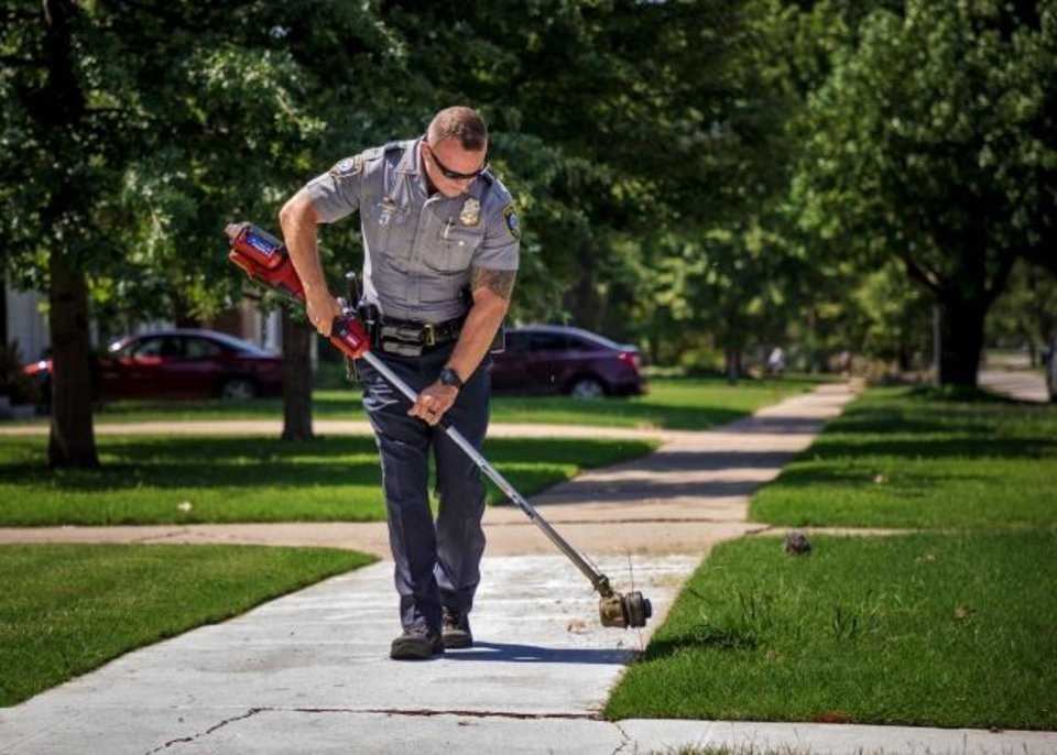 Photo -  Oklahoma City Police Lt. Taylor Shaw helps Rodney Smith edge a yard at an Oklahoma City home, part of Smith's nationwide program called Raising Men Lawn Care Service.