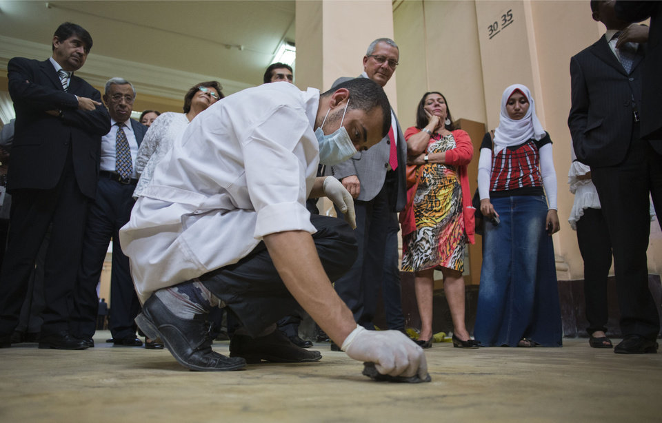Photo - Guests watch a worker clean the floor of the Egyptian Museum in downtown Cairo, Egypt, Friday, Nov. 15, 2013. Egypt unveiled Friday an ambitious renovation project for its Cairo's famed Egyptian Museum, in a bid to show that the Arab world's most populous country was regaining a sense of normalcy after months of unrest. (AP Photo/Hiro Komae)