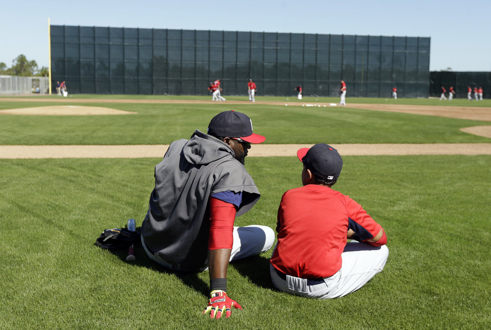Photo - Boston Red Sox designated hitter David Ortiz, left, sits on the field with his son D'Angelo, right, during spring training baseball practice Tuesday, Feb. 18, 2014, in Fort Myers, Fla. (AP Photo/Steven Senne)