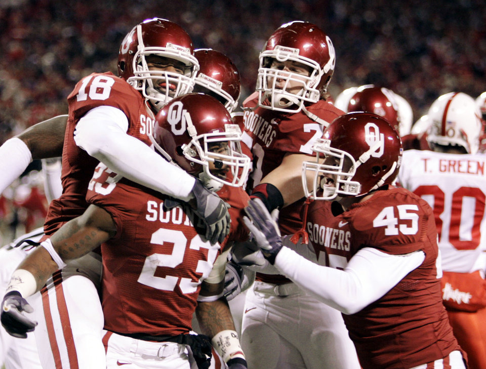 Photo - CELEBRATE, CELEBRATION: Oklahoma Sooner running back Allen Patrick (23) is congratulated by teammates, Jermaine Gresham (18) Chris Messner (79) and Dane Zaslaw (45) after Patrick's touchdown run in the first half of the Big 12 Championship game during the University of Oklahoma Sooners (OU) college football game against the University of Nebraska Cornhuskers (NU) at Arrowhead Stadium, on Saturday, Dec. 2, 2006, in Kansas City, Mo.   By Bryan Terry, The Oklahoman  ORG XMIT: KOD
