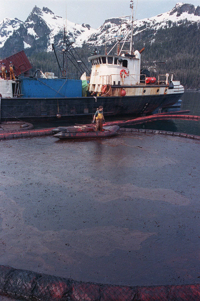 Photo - FILE - In this April 16, 1989, file photo, a clean-up worker rakes through crude oil, contained by floating booms off the waters of Prince William Sound, Alaska. The oil, contained here in Snug Harbor off Knight Island, was later sucked off the water by a U.S. Coast Guard skimmer.  Oil from the tanker Exxon Valdez continues to foul the waters of southern Alaska. Nearly 25 years after the Exxon Valdez oil spill off the coast of Alaska, some damage heals, some effects linger in Prince William Sound. (AP Photo/John Gaps III, File)