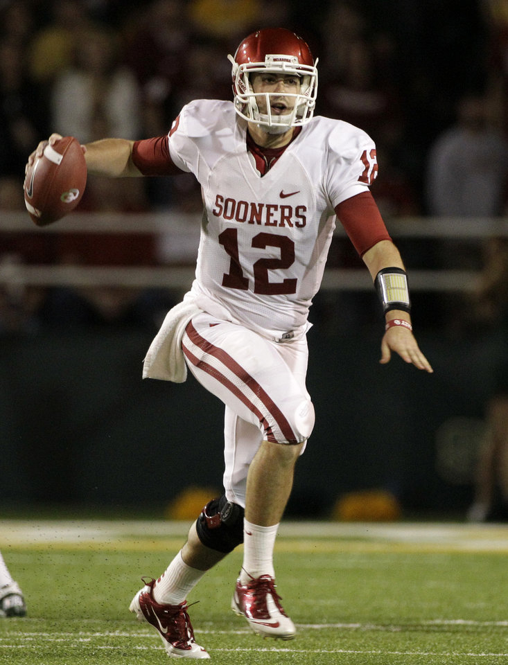 Photo - Oklahoma quarterback Landry Jones (12) scrambles out of the pocket looking for an open receiver in the first half of an NCAA college football game against the Baylor, Saturday, Nov. 19, 2011, in Waco, Texas. (AP Photo/Tony Gutierrez)