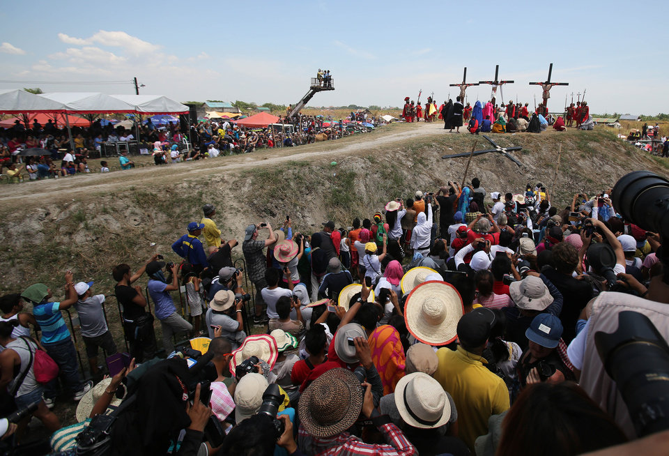 Photo - Spectators watch as Filipino devotee Ruben Enaje, center, stays nailed to a cross with two actors during a play  to re-enact the crucifixion of Jesus Christ in San Pedro Cutud village, Pampanga province, northern Philippines on Friday, April 18, 2014. Church leaders and health officials have spoken against the practice which mixes Roman Catholic devotion with folk belief, but the annual rites continue to draw participants and huge crowds. (AP Photo/Aaron Favila)