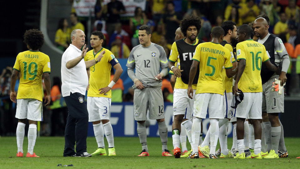 Photo - Brazil's coach Luiz Felipe Scolari, second left, stands with his players after the World Cup third-place soccer match between Brazil and the Netherlands at the Estadio Nacional in Brasilia, Brazil, Saturday, July 12, 2014. The Netherlands won the match 3-0. (AP Photo/Hassan Ammar)