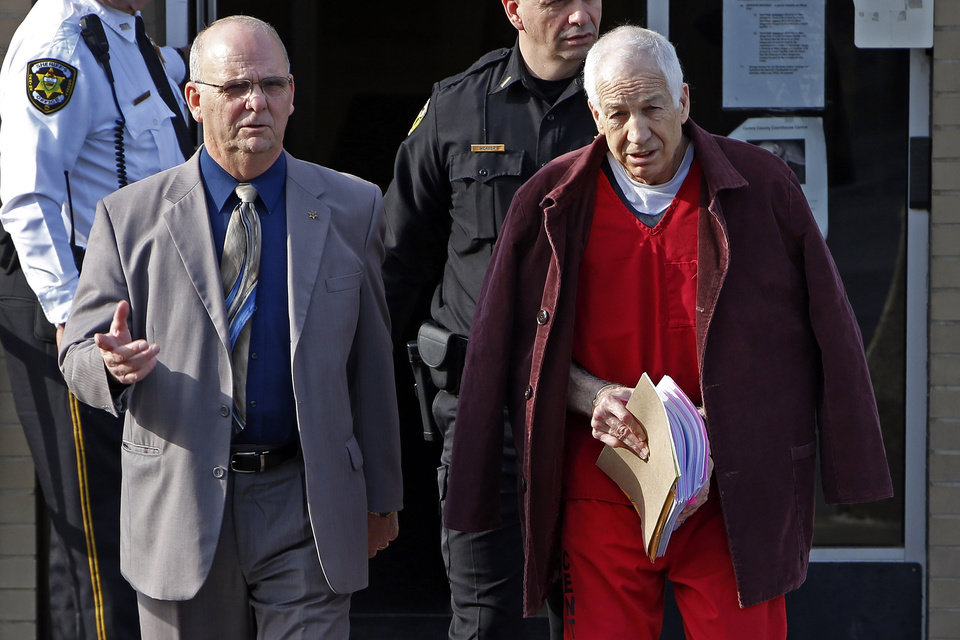 Former Penn State University assistant football coach Jerry Sandusky, left, is essorted by Centre County Sheriff Denny Nau, left, as he leaves the Centre County Courthouse after attending a post-sentence motion hearing in Bellefonte, Pa., Thursday, Jan. 10, 2013. (AP Photo/Gene J. Puskar)