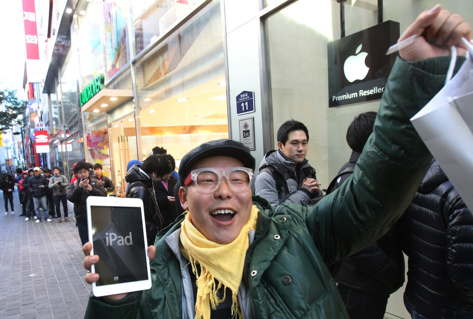 Photo -   FILE -In this Friday, Nov. 2, 2012, file photo, a customer, Song Tae-min reacts after buying a new iPad Mini in Seoul, South Korea. The new iPad Mini is sure to please millions this holiday season. But fans of the latest full-size iPad have reason to look down on this newcomer: compared to other Apple products, the screen just isn't that good. (AP Photo/Ahn Young-joon)