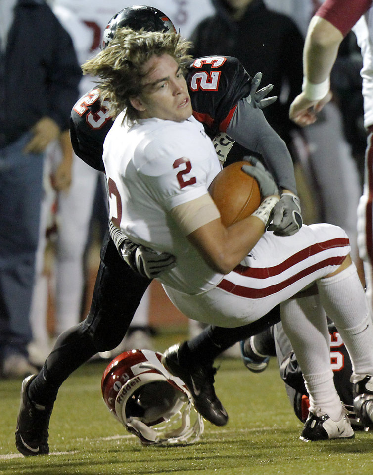 Photo - Owasso's Nick DiMarco loses his helmet as he is hit by Westmoore's Addison Staggs during their playoff game at Moore High School in Moore, Oklahoma, on Friday Nov. 19, 2010. Photo by John Clanton, The Oklahoman