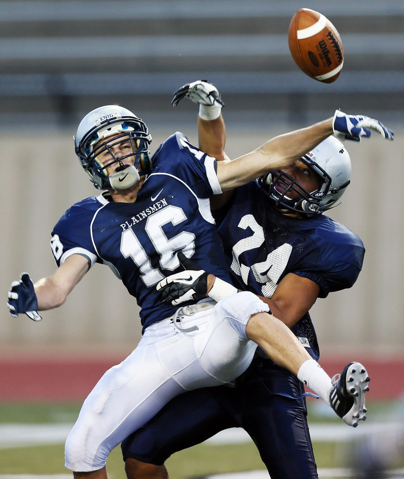 Photo - Enid's Aaron Beagle (16) breaks up a pass intended for Edmond North's Ezel McIntee (24) during a high school football scrimmage at Moore Stadium in Moore, Okla., Friday, Aug. 17, 2012. Photo by Nate Billings, The Oklahoman