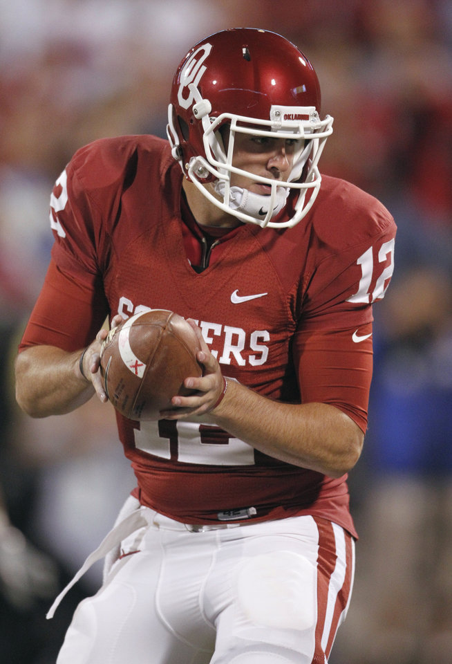 Photo - Quarterback Landry Jones hands off the ball during the first half of the college football game between the University of Oklahoma (OU) Sooners and the University of Colorado Buffaloes at Gaylord Family-Oklahoma Memorial Stadium in Norman, Okla., Saturday, October 30, 2010.  Photo by Steve Sisney, The Oklahoman