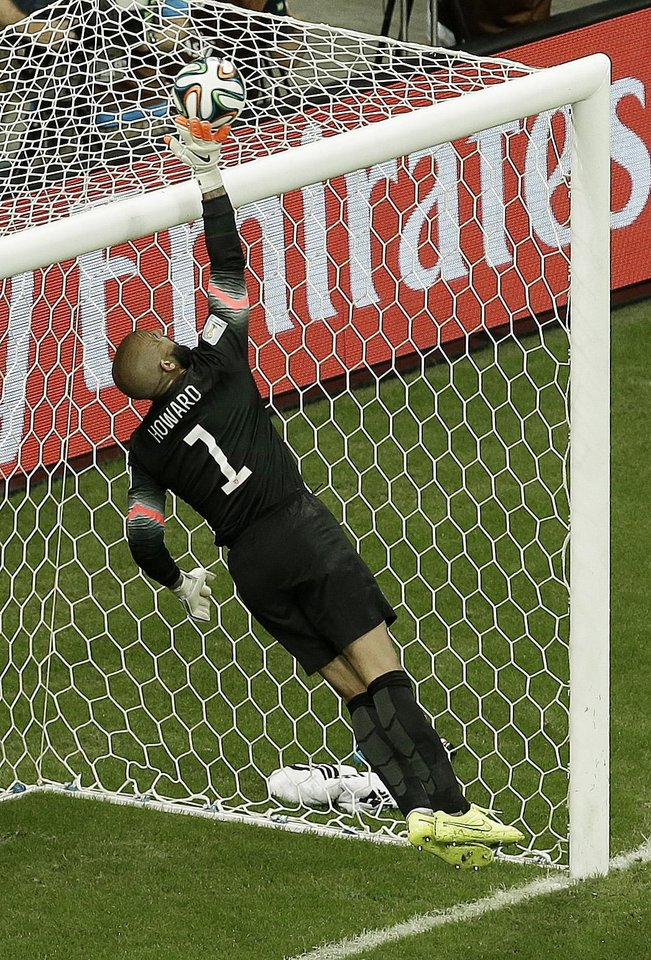 Photo - United States' goalkeeper Tim Howard deflects the ball over the crossbar during the World Cup round of 16 soccer match between Belgium and the USA at the Arena Fonte Nova in Salvador, Brazil, Tuesday, July 1, 2014. (AP Photo/Themba Hadebe)