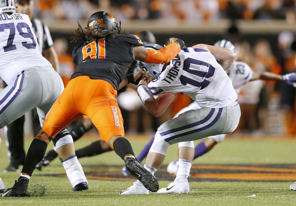 Photo - Kansas State's Skylar Thompson (10) escapes the tackle of Oklahoma State's Mike Scott (91) during the college football game between the Oklahoma State Cowboys and the Kansas State Wildcats at Boone Pickens Stadium in Stillwater, Okla., Saturday, Sept. 28, 2019.  OSU won 26-13. [Sarah Phipps/The Oklahoman]