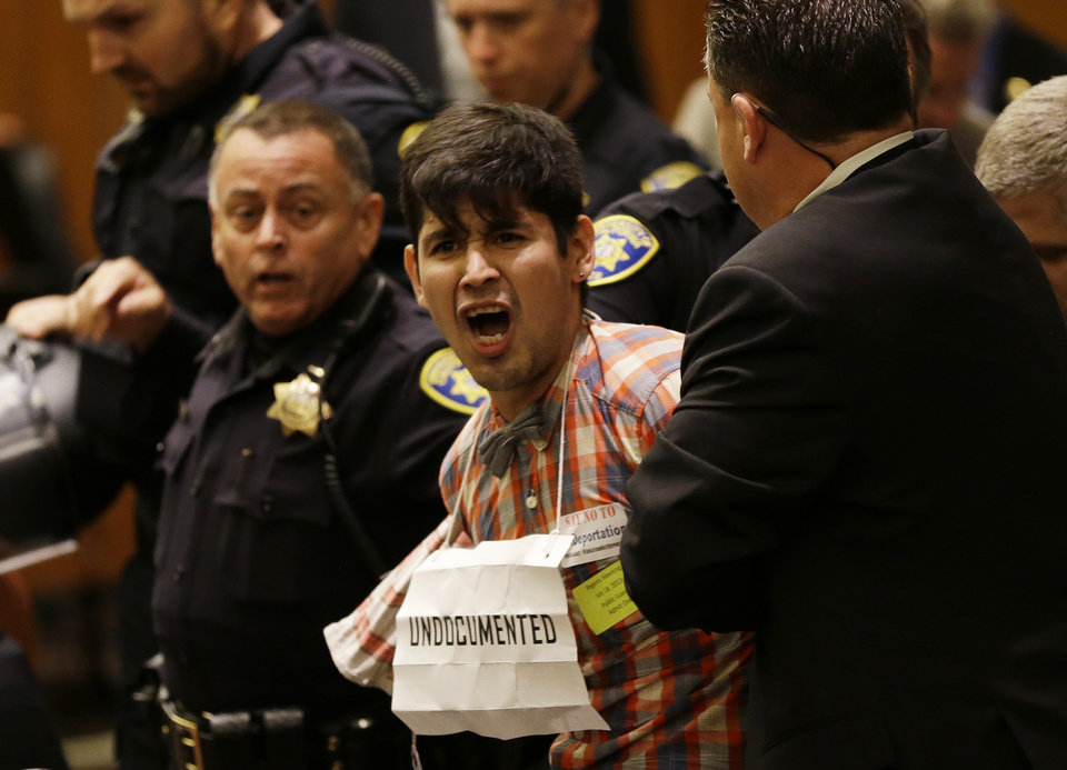 Photo - Protester Alex Aldama is removed by security shortly before Homeland Security Secretary Janet Napolitano was voted in as the next University of California president during a Board of Regents meeting Thursday, July 18, 2013 in San Francisco. The University of California's governing board voted Napolitano to become the system's first female president, but her selection is being criticized by students upset about federal immigration policy and professors concerned about her lack of experience in academia. (AP Photo/Eric Risberg)