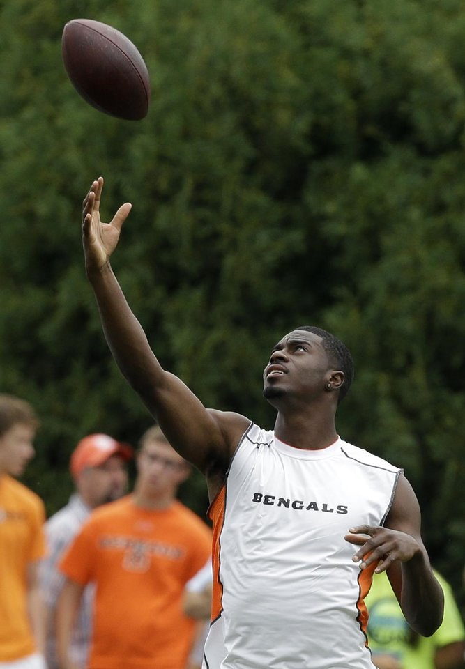 Photo - Cincinnati Bengals wide receiver A.J. Green tosses a ball during practice at the NFL football team's training camp, Wednesday, July 31, 2013, in Cincinnati. Green bruised his knee in practice Friday and hasn't been cleared to return to practice yet. (AP Photo/Al Behrman)