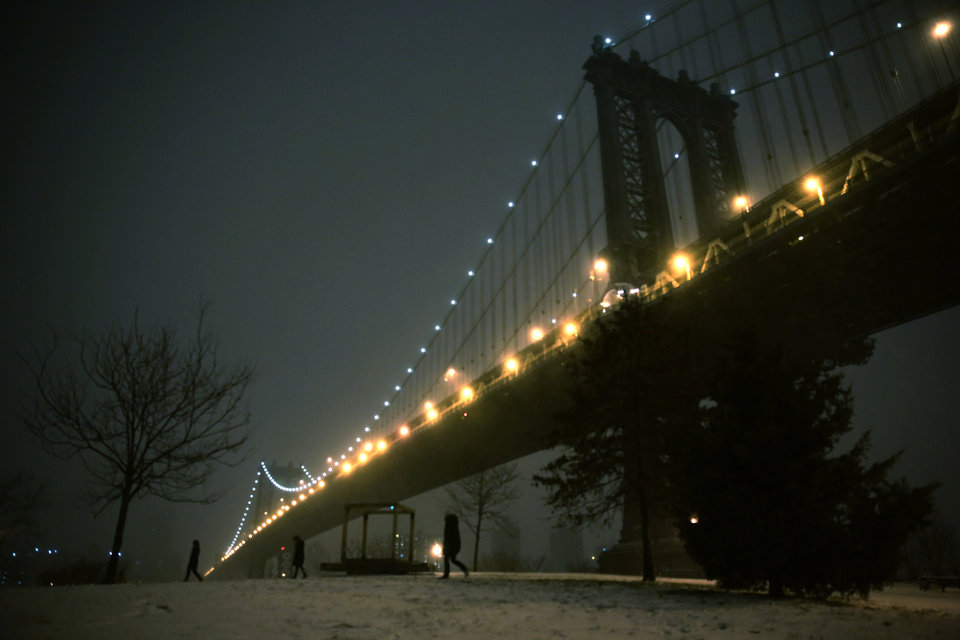 Photo - People walk through a park on the waterfront in Brooklyn near the Manhattan Bridge during a winter storm in New York, Thursday, Jan. 2, 2014. The storm is expected to bring snow, stiff winds and punishing cold into the Northeast on Thursday. (AP Photo/Peter Morgan)