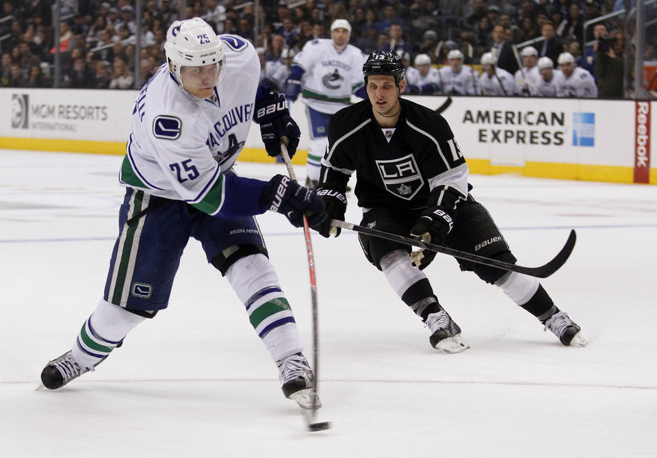 Photo - Vancouver Canucks center Mike Santorelli (25) shoots the puck with Los Angeles Kings left wing Kyle Clifford (13) trailing during the first period of an NHL hockey game on Saturday, Jan. 4, 2014, in Los Angeles. (AP Photo/Alex Gallardo)