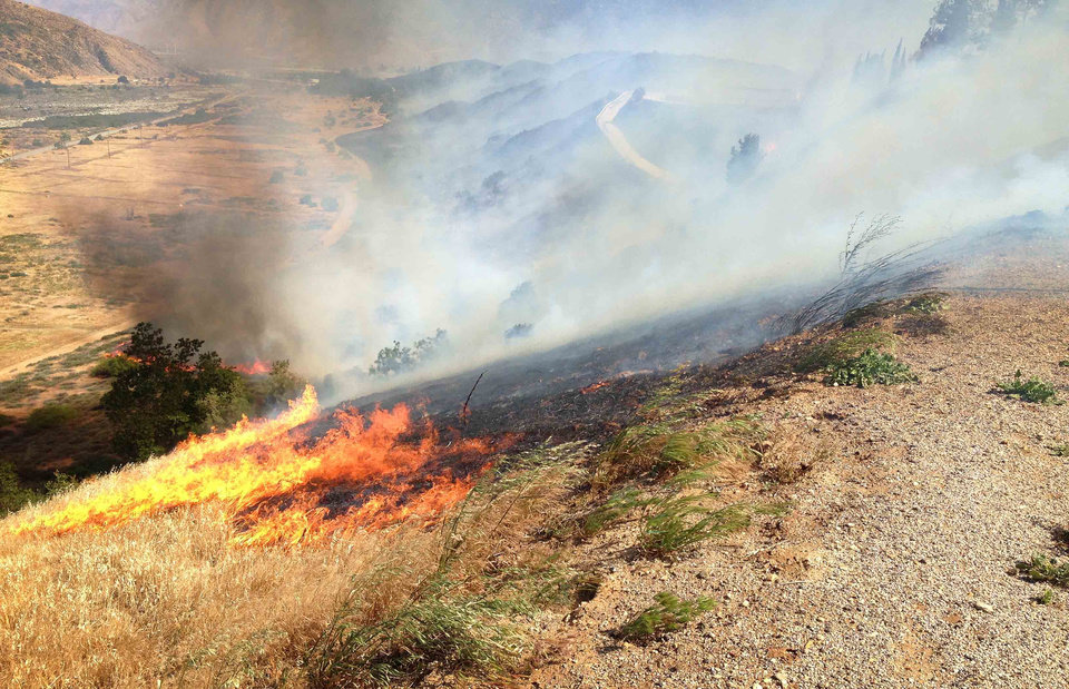 Flames scorch the hillside north of Banning, Calif., as a brush fire burns in the area Wednesday, May 1, 2013. (AP Photo/The Press-Enterprise, Terry Pierson)