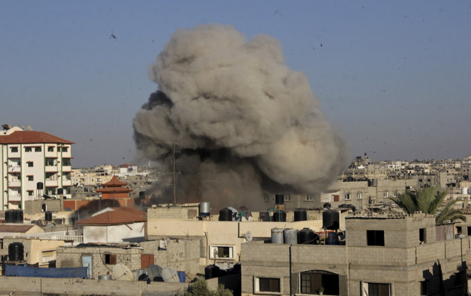 Photo - Smoke, dust and debris rise from an explosion following an Israeli air strike on the house of Nafez Azzam, a leader for Islamic Jihad leader, one hour before the announcement of the cease-fire between Palestinians and Israelis, in Rafah refugee camp, in the southern Gaza Strip, Tuesday, Aug. 26, 2014. (AP Photo/Hatem Ali)