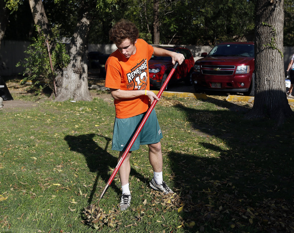 Bishop McGuinness senior Casey Burnstein rakes leaves as part of a community service project at The Sanctuary women's development center, 2133 SW 11 in Oklahoma City.  <strong>SARAH PHIPPS - SARAH PHIPPS</strong>