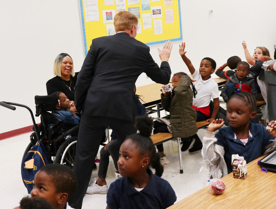 Photo - Sen. James Lankford high fives children in the cafeteria as he takes a tour of Thelma Parks Elementary School in Oklahoma City looking at the RESTORE OKC program there Tuesday, October 8, 2019. [Doug Hoke/The Oklahoman]
