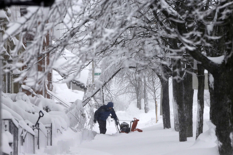 A man clears snow from the front of his home on Third Street in the South Boston neighborhood of Boston on Saturday, Feb. 9, 2013. (AP Photo/Gene J. Puskar)