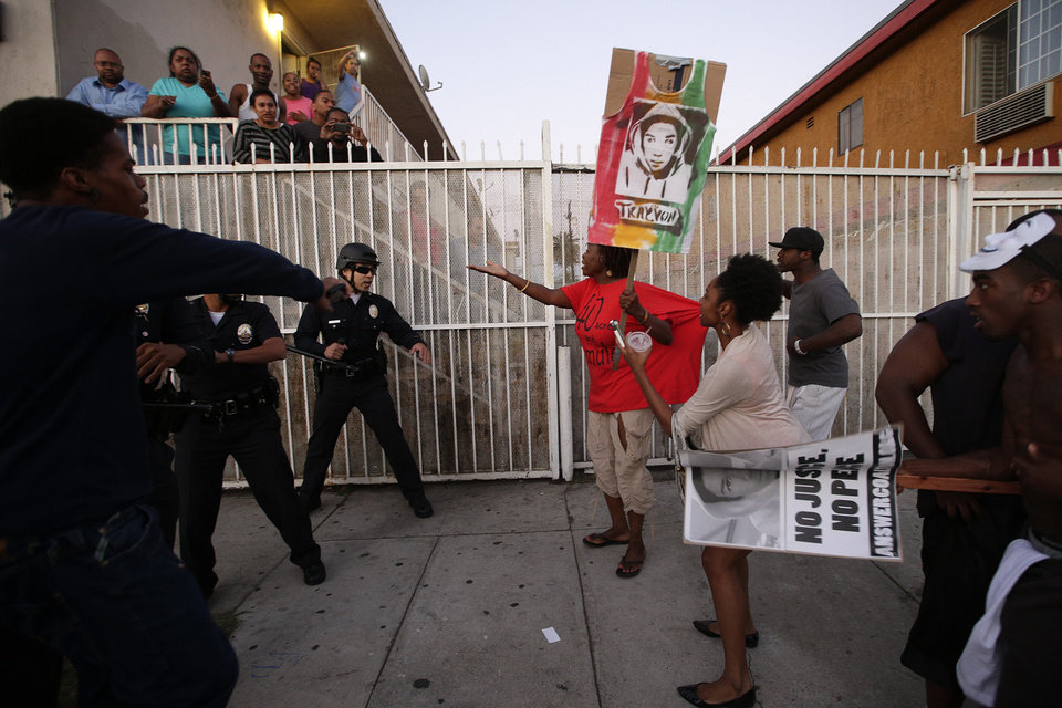 Photo - Protesters confront Los Angles police officers during a demonstration in reaction to the acquittal of neighborhood watch volunteer George Zimmerman on Monday, July 15, 2013, in Los Angeles. Anger over the acquittal of a U.S. neighborhood watch volunteer who shot dead an unarmed black teenager continued Monday, with civil rights leaders saying mostly peaceful protests will continue this weekend with vigils in dozens of cities. (AP Photo/Jae C. Hong)
