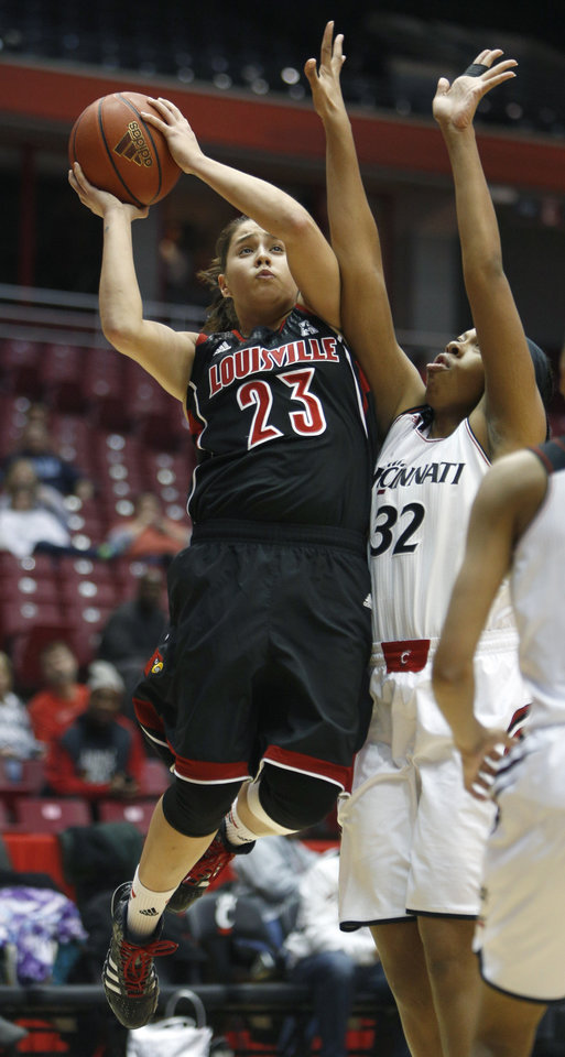 Photo - Louisville guard Shoni Schimmel (23) goes up for a shot against Cincinnati forward Shelbi Chandler (32) during the first half of an NCAA college basketball game, Saturday, March 1, 2014, in Cincinnati. (AP Photo/David Kohl)