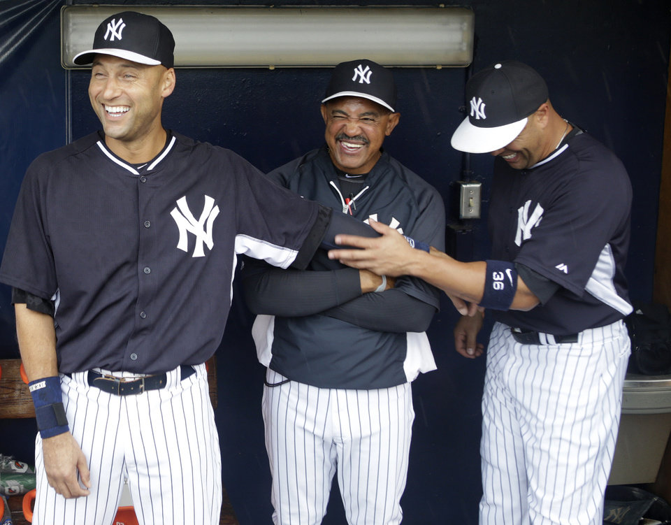 Photo - New York Yankees shortstop Derek Jeter, left, clowns around in the dugout with bench coach Tony Pena, center, and teammate Carlos Beltran before an exhibition baseball game against the Miami Marlins in Tampa, Fla., Saturday, March 29, 2014.  The game was called due to rain. (AP Photo/Kathy Willens)