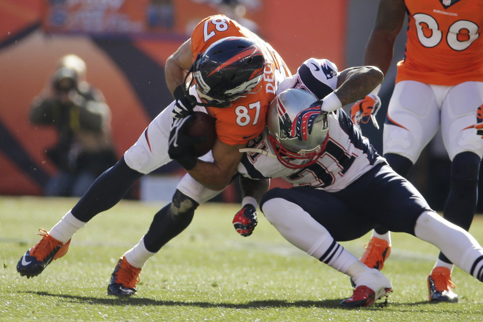 Photo - Denver Broncos wide receiver Eric Decker (87) is stopped New England Patriots cornerback Aqib Talib (31) during the first half of the AFC Championship NFL playoff football game in Denver, Sunday, Jan. 19, 2014. (AP Photo/Charlie Riedel)