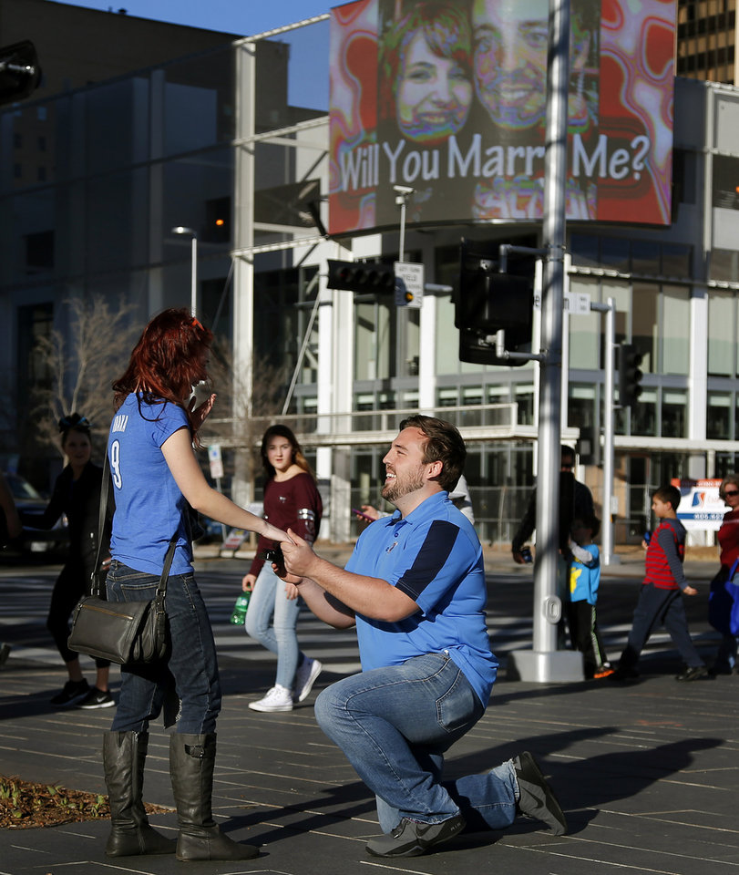 Photo - Ben Edison proposes to his girlfriend Allyson Bond with the help of the Oklahoman's big screen on the corner of Robinson and Sheridan in Oklahoma City, Saturday, Feb. 14, 2015. Photo by Bryan Terry, The Oklahoman