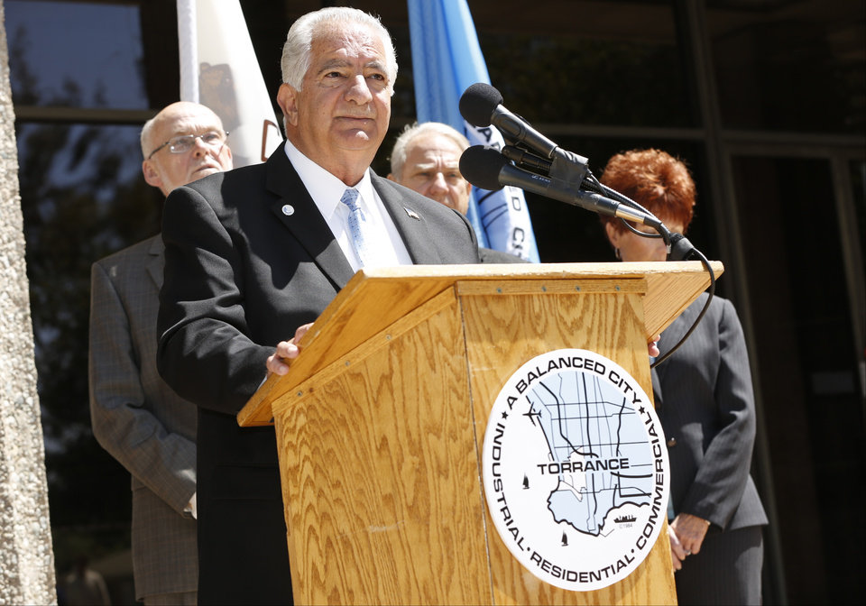Torrance Mayor Frank Scotto, at podium, holds a news conference to discuss the announced relocation of Toyota Motor Sales' U.S. headquarters, Monday, April 28, 2014, in front of City Hall in Torrance, Calif.  Toyota said that it will move its U.S. headquarters from Torrance to Plano, Texas, a suburb of Dallas. Small groups of employees will start moving to temporary office space there this year, but most will not move until late 2016 or early 2017 when a new headquarters is completed.  (AP Photo/Damian Dovarganes)