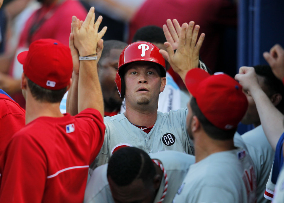 Photo - Philadelphia Phillies Reid Brignac (17) celebrates with teammates after scoring off a double by teammate Cesar Hernandez (16) in the fourth inning of a baseball game Tuesday, June 17, 2014, in Atlanta. (AP Photo/Todd Kirkland)
