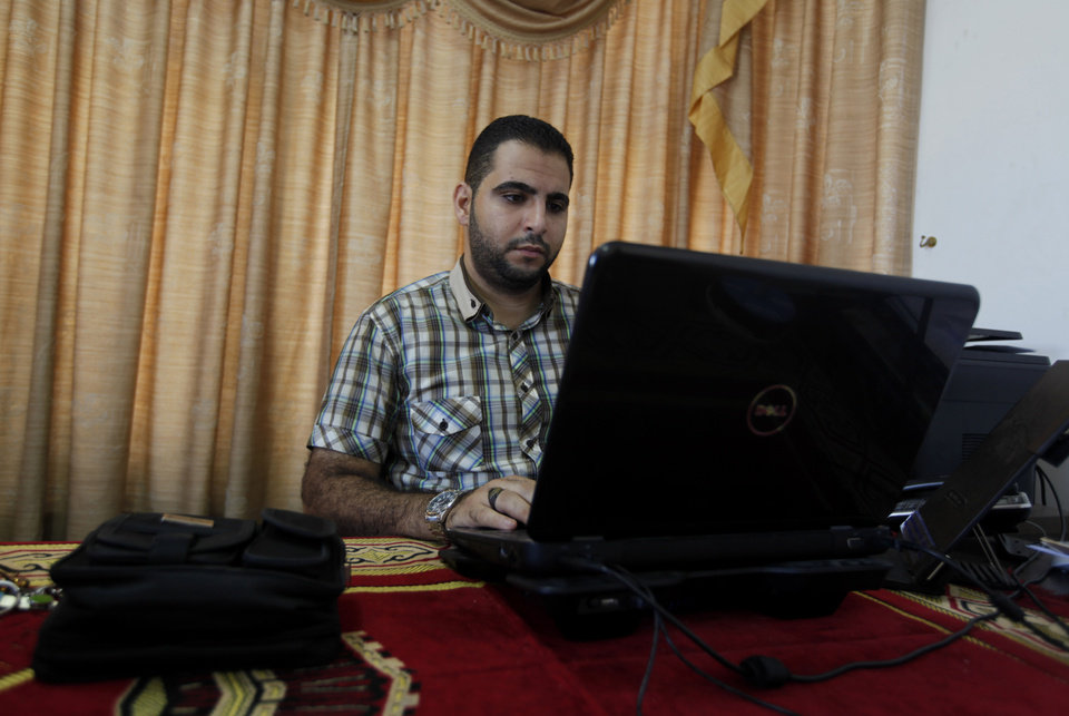 Photo - In this Saturday, July 28, 2013 photo Baraa Rantisi, 23, reads a news article on clashes in Egypt at his house office in Gaza City. On the day of his induction, Baraa Rantisi was told to wait near a mosque. A white car drove up. Secret passwords were exchanged. And then he was sworn into the Muslim Brotherhood, an exclusive movement that sees itself on a divine mission to establish Islamic rule. AP reporters got rare access to the Rantisi family, the closest thing to a royal clan in the Brotherhood in Gaza, at a time when the movement is under siege throughout the region. (AP Photo/Hatem Moussa)