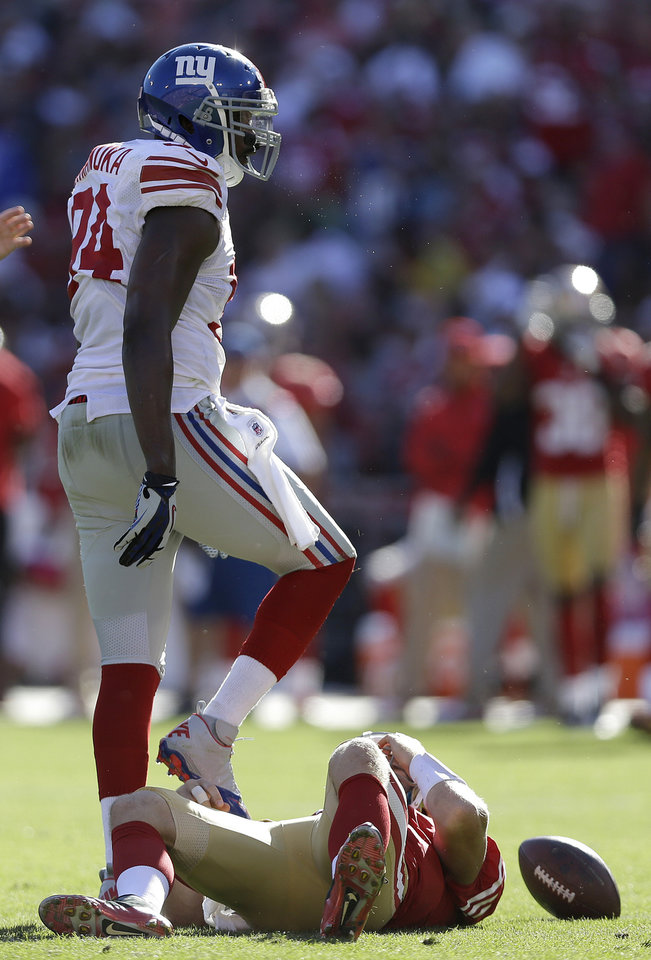 Photo -   New York Giants outside linebacker Mathias Kiwanuka (94) stands over San Francisco 49ers quarterback Alex Smith (11) after sacking him during the fourth quarter of an NFL football game in San Francisco, Sunday, Oct. 14, 2012. The Giants 26-3. (AP Photo/Marcio Jose Sanchez)
