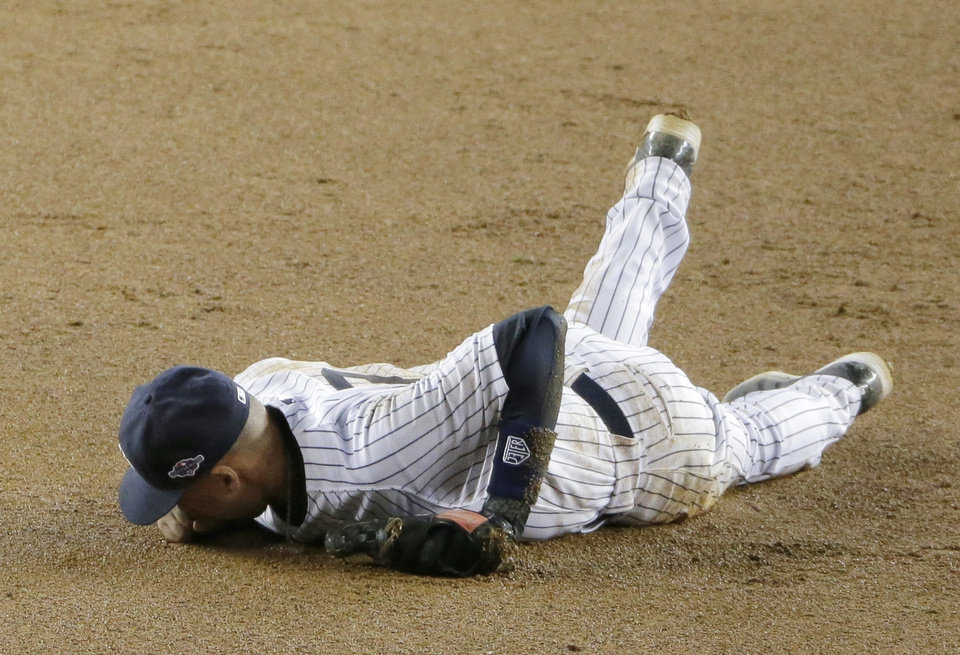 Photo -   New York Yankees shortstop Derek Jeter lays on the infield after injuring himself in the 12th inning of Game 1 of the American League championship series against the Detroit Tigers Sunday, Oct. 14, 2012, in New York.(AP Photo/Charlie Riedel)